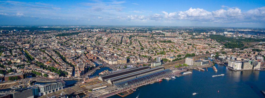 https://www.dembozaak.nl/wp-content/uploads/2020/10/city-aerial-view-over-amsterdam-P69ZGRG-scaled-1024x380.jpg